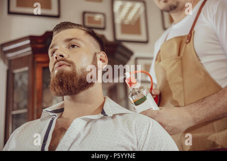 Man with beard uses the services of a barber.  Photo in vintage style - Stock Photo