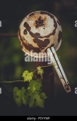 old rusty ladle hanging on the vineyard in the garden - Stock Photo