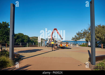 A truck and its driver unloading bollards with a crane to prevent vehicle access to the jetty, Jetty Beach, Coffs Harbour, New South Wales, Australia - Stock Photo