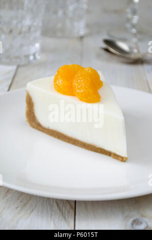 Cheesecake with slices of mandarin on white plate - Stock Photo