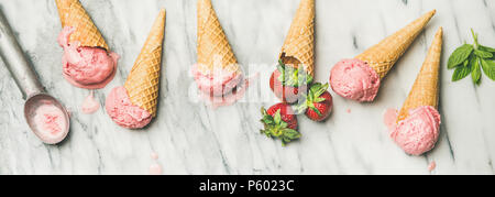 Flat-lay of homemade yogurt strawberry ice cream in waffle cones - Stock Photo