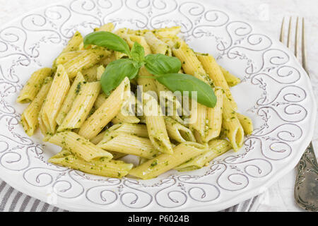 Closeup of plate with penne rigate pasta with basil pesto. - Stock Photo