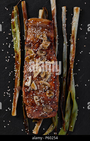 Roasted salmon fillet on a bed of spring onions, glazed with balsamic vinegar, garlic, and sesame seeds. Black wooden background, top view shot. - Stock Photo