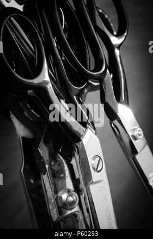 Collection of scissors in black and white hanging up in a workshop - Stock Photo