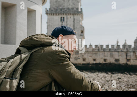 Portrait of a young tourist guy or traveler man with a backpack that sits and stares into the distance in Lisbon in Portugal. Belem Tower in the background - Stock Photo