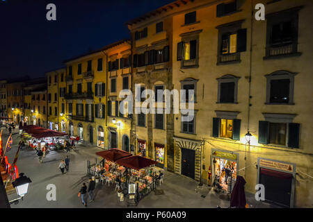 Tourists enjoy a late night on the Via Santa Maria, the busy tourist street leading to the Leaning tower of Pisa in the Tuscany region of Italy. - Stock Photo