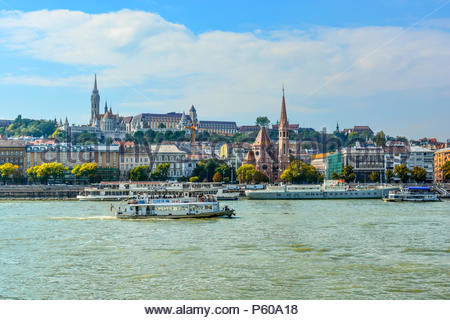 The Szilágyi Dezso Square Reformed Church on the banks of the Danube River in Budapest Hungary with the Castle District, St Matthias Church above - Stock Photo