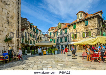 Tourists enjoy cafes and shops on an early autumn afternoon on the Fruit Square in the Diocletian's Palace section of Old Town Split, Croatia. - Stock Photo