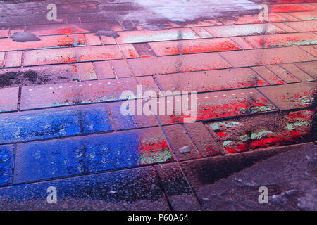 A neon American flag is reflected on the wet sidewalk of Times Square in Manhattan, New York City - Stock Photo