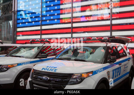 NYPD vehicles in front of a neon stars and stripes in Times Square in New York City - Stock Photo