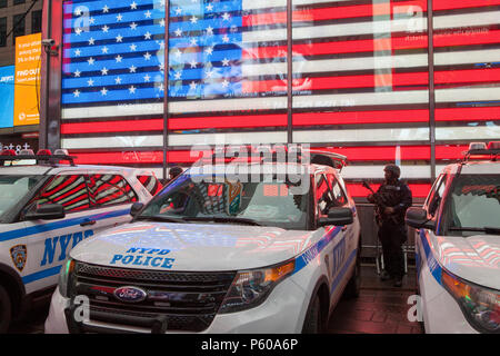 An armed NYPD cop stands in front of a neon stars and stripes in Times Square in New York City - Stock Photo