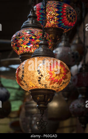 Colourful patterned lamps, in the traditional Moroccan design, hang from a stall in a Marrakech souk. The lamps are lit up. - Stock Photo