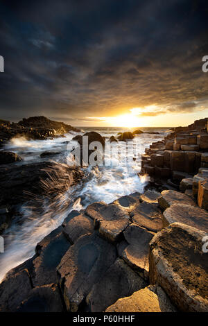 Waves crashing into Giant's Causeway at Sunset - Stock Photo