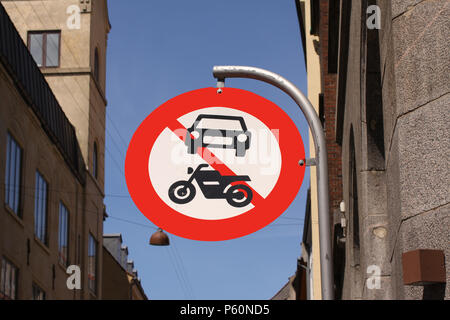 The passage of vehicles and motorcycles is prohibited. Round red and white traffic sign in a city with blue sky background. - Stock Photo