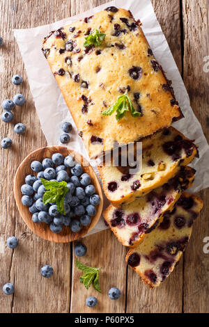Dessert sliced fresh blueberry bread muffin cake with mint closeup on the table. vertical top view from above - Stock Photo