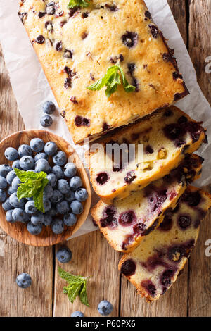 fresh blueberry loaf of bread muffin cake with mint closeup on a table. vertical top view from above - Stock Photo