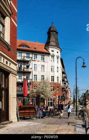 Berlin Prenzlauer Berg,Street view in spring with old gabled apartment buildings and blossoms on trees - Stock Photo