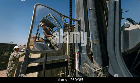 AQABA, Jordan (April 4, 2016) – Equipment Operator 2nd Class Anthony Arredondo, from Naval Mobile Construction Battalion 133, Detachment Bahrain, sets up a barrier on Camp Badger during International Mine Countermeasures Exercise (IMCMEX) 2016. IMCMEX is a U.S. Naval Forces Central Command led multilateral exercise utilizing all aspects of defensive maritime warfare including mine countermeasures, maritime security operations and maritime infrastructure protection. IMCMEX serves to demonstrate the global resolve in maintaining freedom of navigation and the free flow of maritime commerce from t - Stock Photo