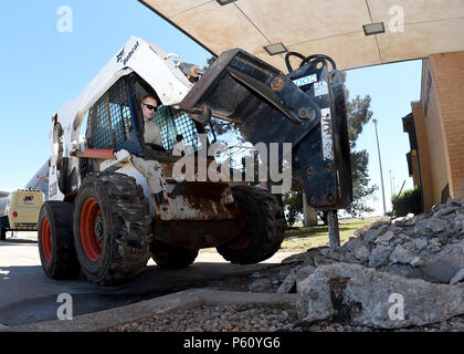 U.S. Air Force Senior Airman Sean Duddy, 97th Civil Engineer Squadron heavy equipment operator, uses a skid steer with a jack hammer attachment to breaks up a set of concrete stairs outside Base Operations, April 4, 2016, at Altus Air Force Base, Okla. The stairs were renovated to prevent any possible injury occurring from a crack that formed. (U.S. Air Force photo by Airman 1st Class Kirby Turbak/Released) - Stock Photo