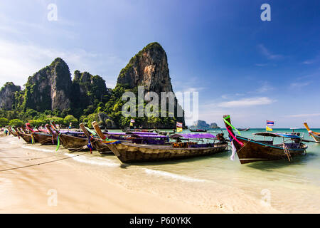 ocean seashore with island and boat on water at sunset in Krabi, Thailand - Stock Photo