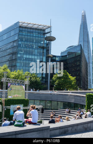 Lond, UK, 27 June 2018. The heatwave continues in central London with clear blue skies and potentially record breaking temperatures. Crowds of tourists and office workers at more london place and Tower bridge enjoying the hot weather and the beautiful sunshine sitting on the grass and sunbathing. Credit: Steve Hawkins Photography/Alamy Live News - Stock Photo