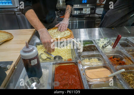 New York, USA, 27 June 2018. Employees construct a pizza right before the customers' eyes in assembly line fashion on opening day of Oath Pizza in their first New York pizzeria on Wednesday, June 27, 2018. Oath Pizza constructs its avocado oil seared crust pizzas in a Chipotle style manner with the toppings put on catering to customers' individual preferences which is then cooked via a conveyor belt oven. This is the first location of the 10 store Massachusetts based chain in New York, with another opening in NY soon and one open in Virginia. (© Richard B. Levine) Credit: Richard Levine/Alamy - Stock Photo