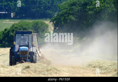 Ripe, East Sussex, UK. 28th June 2018. Dust rises from bone dry fields as a farmer makes hay whilst the sun shines. The South East has seen one of the driest junes on record. © Peter Cripps/Alamy Live News - Stock Photo
