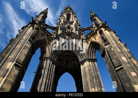 Looking up to the soot stained stones of the Sir Walter Scott Monument of Victorian Gothic architecture in Edinburgh Scotland UK with blue sky - Stock Photo