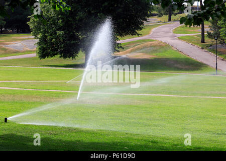 Sprinklers in park water the grass on a hot day of summer in Finland. - Stock Photo