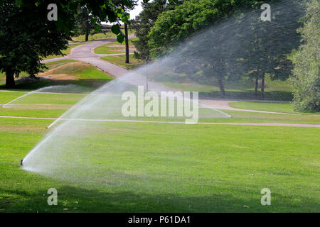 Sprinklers in park watering the grass on a hot day of summer in Finland. - Stock Photo