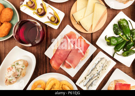 The food of Spain. An overhead closeup photo of various Spanish tapas, shot from above on a dark rustic texture. Jamon, cheese, wine, calamari rings,  - Stock Photo
