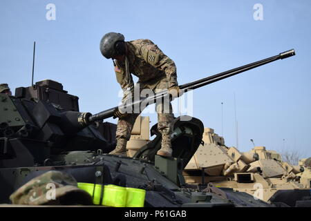 Soldiers from 1st Battalion, 64th Armor Regiment perform Preventive Maintenance Checks and Services on an M2A3 Bradley Infantry Fighting Vehicle as they draw equipment from the European Activity Set at Mihail Kogălniceanu Air Base, Romania April 7. PMCS is a precursor of signing for the equipment, which the battalion will use to shoot gunnery in Romania to prepare the battalion to join over 25,000 participants from 24 countries for Exercise Anakonda 16 in Poland. Anakonda 16 is a Polish national exercise that seeks to train, exercise and integrate Polish national command and force structures - Stock Photo