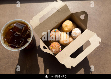 A box of Timbits served with iced coffee at a Tim Hortons store in Canada. Timbits are, essentially, flavoured doughnut pieces. - Stock Photo