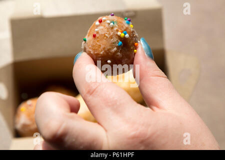 A box of Timbits served at a Tim Hortons store in Canada. Timbits are, essentially, flavoured doughnut pieces. - Stock Photo