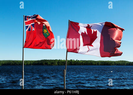 The flags of the province of Ontario and Canada flying by Marble Lake in Ontario, Canada. The Canadian flags bears a maple leaf emblem. - Stock Photo