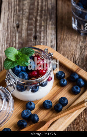 Cheesecake creme parfaits with blueberries and red currant berries served in jar, delicious summer no-bake dessert on rustic wooden table ready to eat - Stock Photo