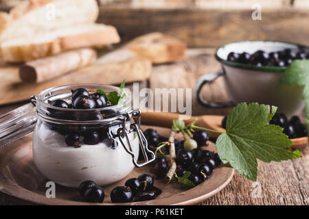 Cheesecake creme parfaits with fresh black currant in jar, delicious summer no-bake dessert on rustic wooden table ready to eat - Stock Photo