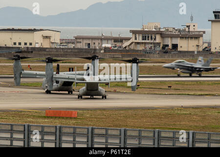 Two MV-22B Ospreys from Marine Medium Tiltrotor Squadron (VMM) 265 (Reinforced)  attached to the 31st Marine Expeditionary Unit wait to take off as an F/A-18 Hornet lands at Marine Corps Air Station Iwakuni, Japan, in support of the Government of Japan's relief efforts following the devastating earthquake near Kumamoto April 18, 2016. The long-standing relationship between Japan and the U.S. allows U.S. military forces in Japan to provide rapid, integrated support to the Japan Self-Defense Forces and civil relief efforts. (U.S. Marine Corps photo by Lance Cpl. Aaron Henson/Released) - Stock Photo