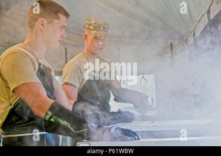Spc. Maxim Trifonov, a motor transport operator with the 733rd Transportation Company, left, and Spc. Ezra Utting, also with the 733rd T.C., sanitize cooking utensils for the food services specialists competing in the annual Philip A. Connelly Award competition at Fort Indiantown Gap, Pa., April 23, 2016. (U.S. Army photo by Staff Sgt. Dalton Smith / Released) - Stock Photo