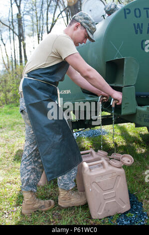 Spc. Maxim Trifonov, a motor transport operator with the 733rd Transportation Company, fills two water cans for cooking utensil sanitization during the annual Philip A. Connelly Award competition at Fort Indiantown Gap, Pa., April 23, 2016. (U.S. Army photo by Staff Sgt. Dalton Smith / Released) - Stock Photo