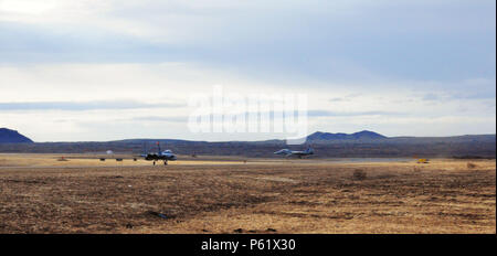 Two U.S. Air Force F-15C Eagle fighter aircraft taxi the runway at Keflavik International Airport, April 6, 2016. Four F-15C Eagles from the 131st Fighter Squadron and 194th Fighter Squadron, Air National Guard Base, Calif., along with approximately 200 Airmen are deployed to Iceland to conduct Icelandic Air Surveillance operations throughout April. (U.S. Air Force photo by Master Sgt. Kevin Nichols) - Stock Photo