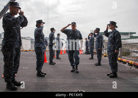SASEBO, Japan (April 7, 2016) – Commander, Expeditionary Strike Group (ESG) 7, Rear Adm. John B. Nowell Jr. salutes sideboys as he enters the quarterdeck aboard amphibious assault ship USS Bonhomme Richard (LHD 6). Bonhomme Richard is the lead ship of the Bonhomme Richard Amphibious Ready Group and is forward-deployed in the U.S. 7th Fleet area of operation. (U.S. Navy photo by Mass Communication Specialist 3rd Class Jeanette Mullinax/Released) - Stock Photo