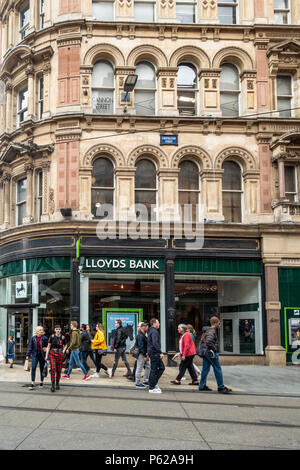 Pedestrians walking in Corporation Street in Birmingham City Centre, outside a Lloyds Bank branch; West Midlands, England, UK - Stock Photo