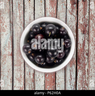 Black currants in a white ceramic bowl. Top view. Ripe and tasty currants on a wooden background. Black currants on wooden table with copy space - Stock Photo
