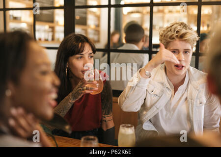 Diverse young girlfriends hanging out together in a trendy bistro - Stock Photo