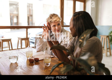 Waiter talking with customers seated at a bistro table - Stock Photo