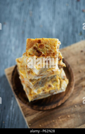 some pieces of typical tortilla de patatas, spanish omelet, on a wooden plate, placed on a gray rustic wooden table - Stock Photo