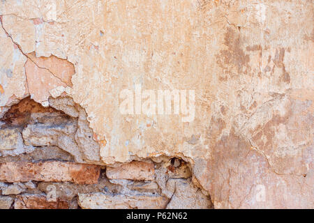 Old Cracked Weathered Shabby Yellow Painted Plastered Peeled Brick Wall Background. - Stock Photo