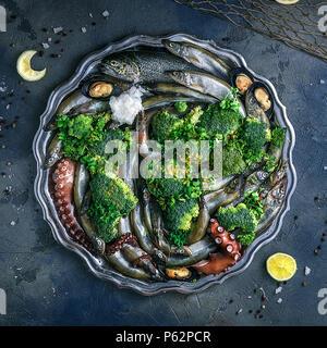 Variety of fresh seafood on a plate with green vegetables - Stock Photo