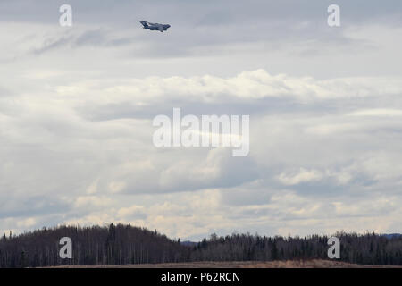 A U.S. Air Force C-17 Globemaster III transporting paratroopers assigned to the 4th Brigade Combat Team (Airborne), 25th Infantry Division, U.S. Army Alaska, approaches Malemute drop zone at Joint Base Elmendorf-Richardson, Alaska, April 5, 2016. The paratroopers of 4/25 were practicing a forced-entry parachute assault. (U.S. Air Force photo/Alejandro Pena) - Stock Photo